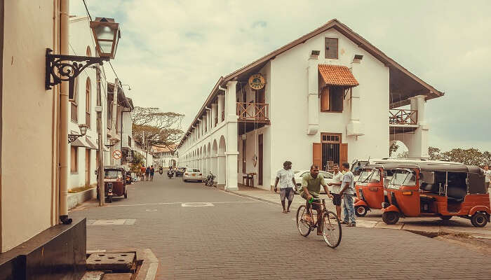 a man cycling in an old town of Sri Lanka