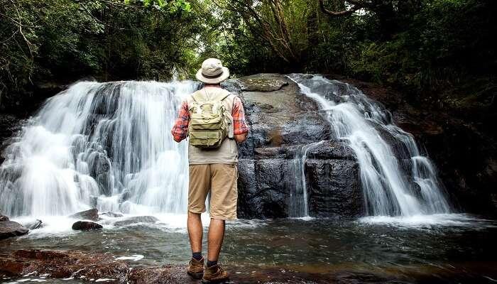 a man standing near a waterfall