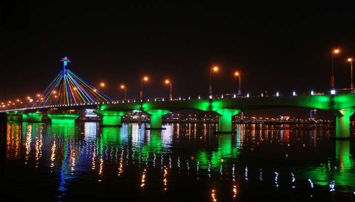 Lit up bridge over a river at night