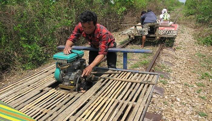person pulling a bamboo train
