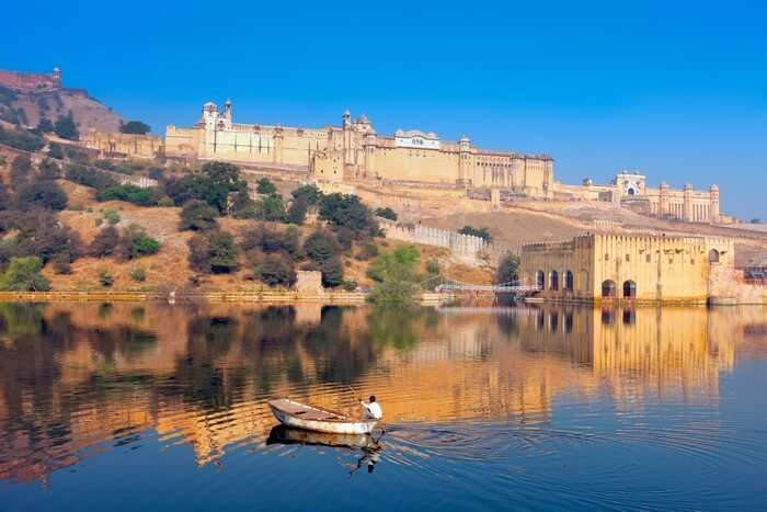 An oarsman rows a boat in the Maota lake in front of Amber fort