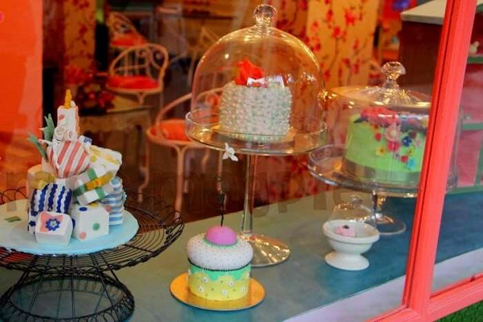 delicious cakes and muffins displayed on the window of Mrs. Magpie bakery