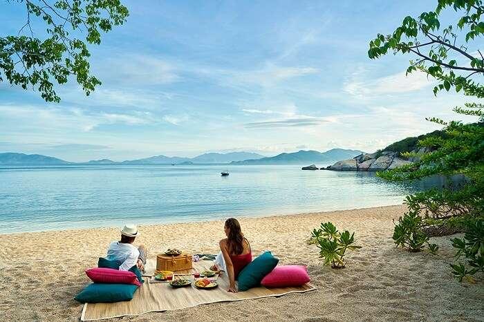 A couple enjoying a beach picnic at Six Senses Ninh Van Bay
