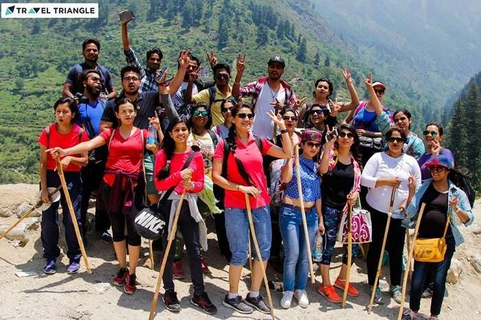 A group of travelers pose after completing a trek in Kasol