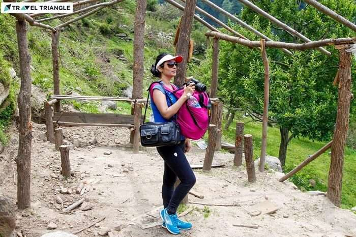 A woman traveler gets ready to capture the beauty of Kasol in her camera