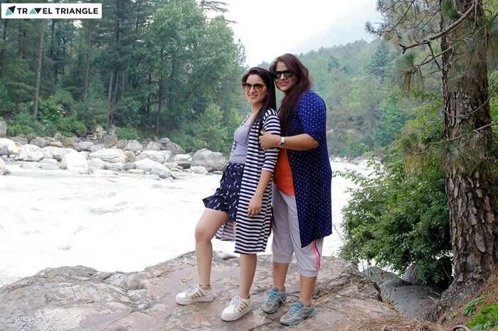 Women travelers pose on the banks of a river flowing through Kasol
