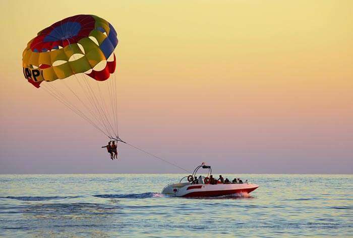 A couple parasailing, a prominent water sport at Alappuzha Beach in Alleppey