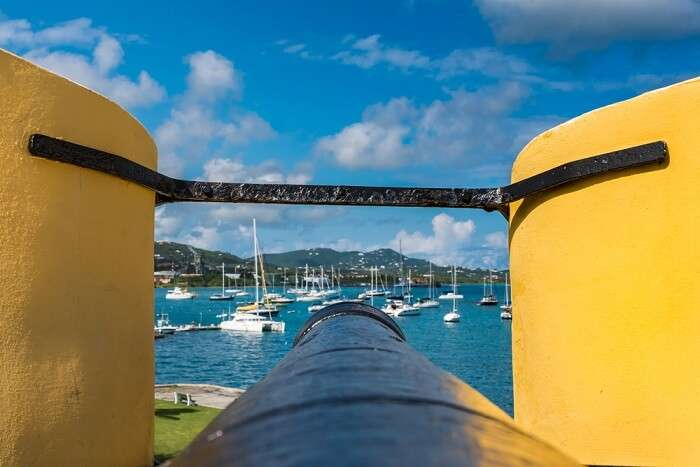 Tip of a vintage cannon through the turret facing the sailboats in the US Virgin Islands