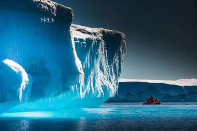 Scientists exploring the icebergs of Antarctica by a boat