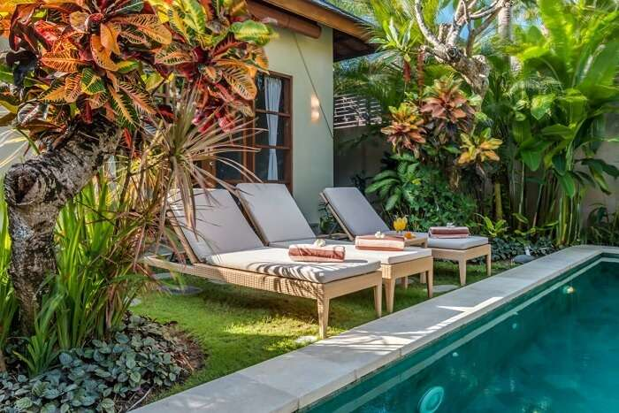 recliners near private pool of luxurious villa essence