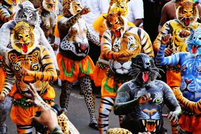 Performers dancing during Puli Kali in Thrissur