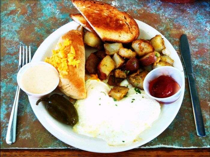 Brazilian plate full of meat, corn beef, tousled egg whites, and bread toasts with cheese.
