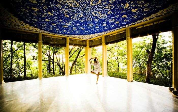A girl practicing yoga in Ananda in Himalayas one of the luxurious yoga retreats in india