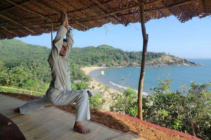 A man performing surya namaskar at SwaSwara Yoga center in Gokarna