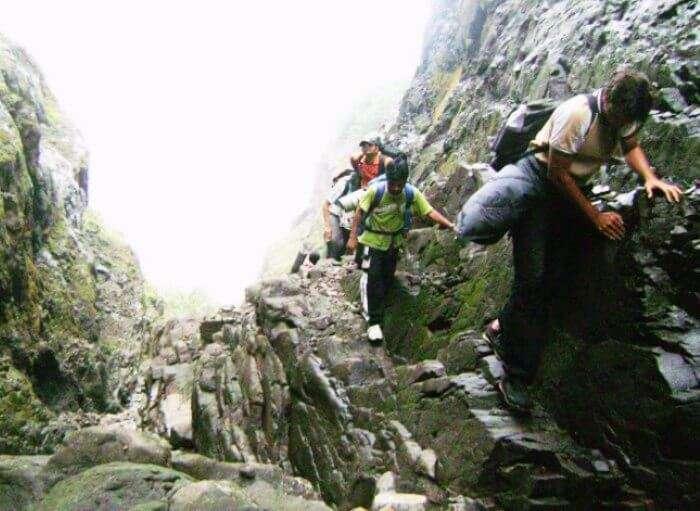 Trekkers climbing the rocks of Harishchandragad Fort
