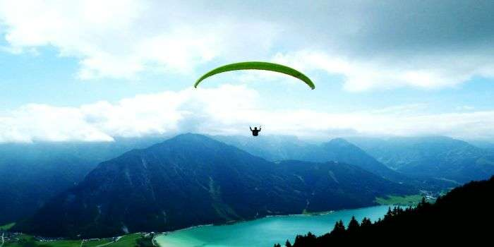 A skydiver glides over the picturesque landscapes as he lands.