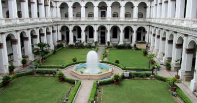 a fountain in the middle of a garden surrounded by a building