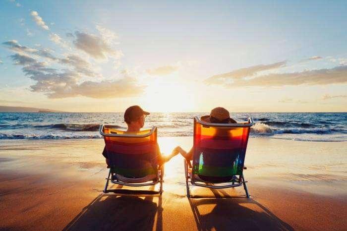 A couple enjoying the sunset on their beach honeymoon