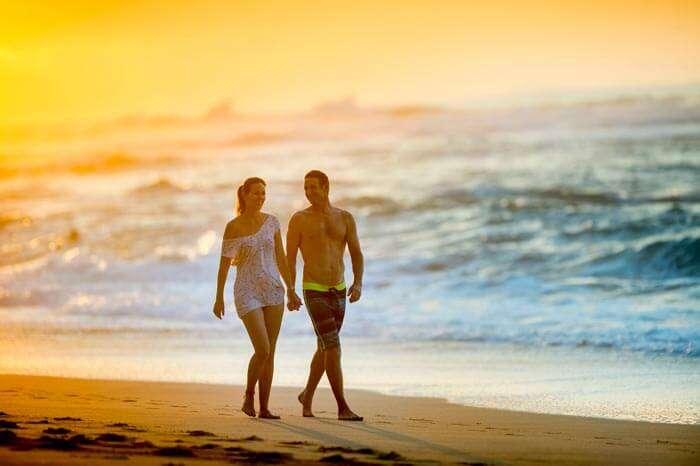 A couple taking an evening walk on the beach of Kauai, Hawaii