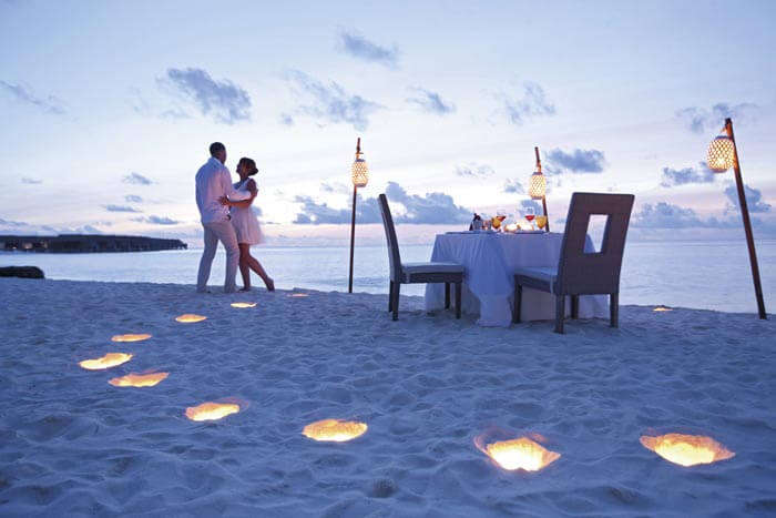 A couple enjoying dinner on a private beach at Maldives