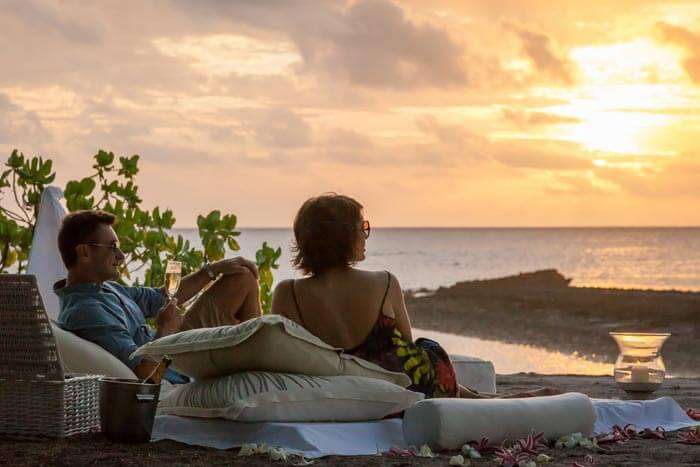A couple relaxing on the beach at The Seychelles