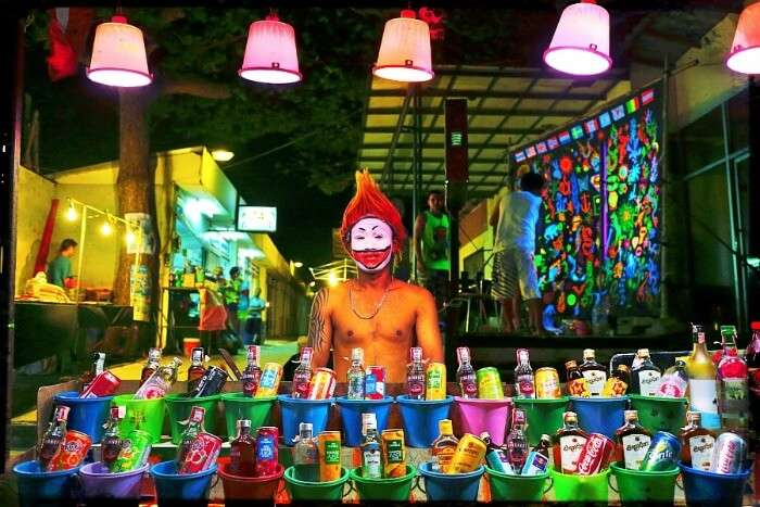 Person with face painting selling buckets in Full Moon Party in Thailand
