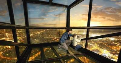 Mother and child enjoy views of the city of Melbourne from a glass deck