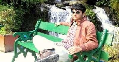 Bala sitting on a bench near a waterfall on his Sikkim-Darjeeling trip