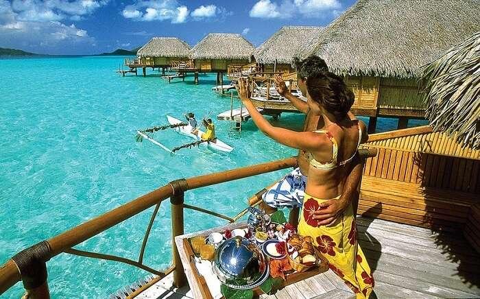 A couple enjoys stay at one of the overwater villas on their Bora Bora honeymoon