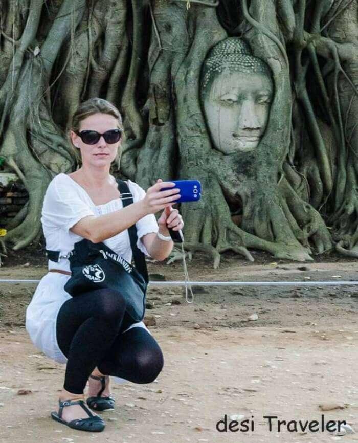 Women posing beside Buddha head in tree roots Thailand
