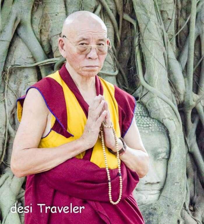 Buddhist monk at Buddha Head tree roots Thailand