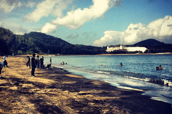 Tourists enjoying at the unique black sand beach of Macau