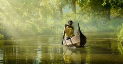 A many rowing a canoe on the backwaters of Alleppey