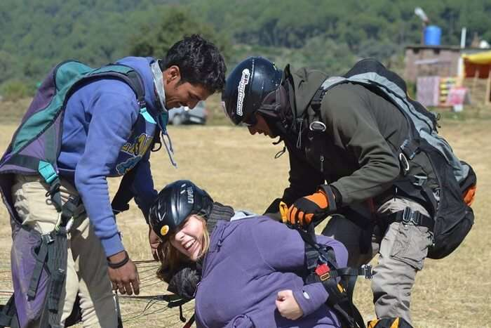 A female tourist getting her parachute removed at the landing site after paragliding in Bir Billing