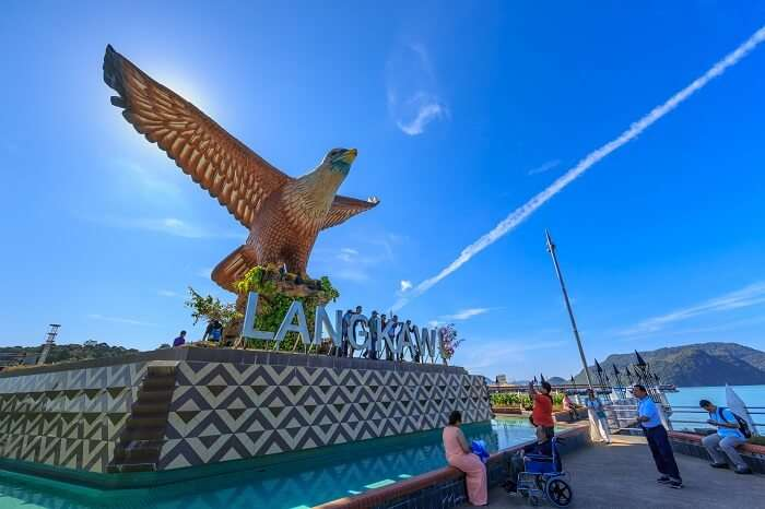 Tourists sit and relax at the 12 meter-tall Eagle Square in Langkawi