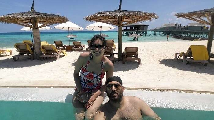 Angad and his wife by the pool at their resort