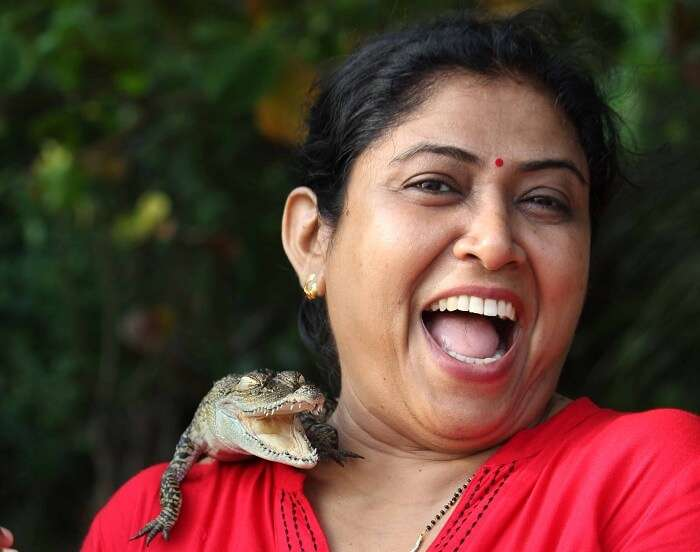Kanikas mother with a baby crocodile on her shoulder