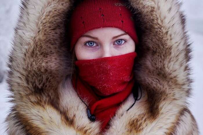 A young girl clad in thick wollens waiting for a school bus in Oymyakon during winters