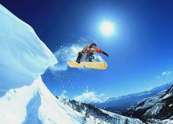 Indulge in the thrilling activity of snowboarding in Manali
