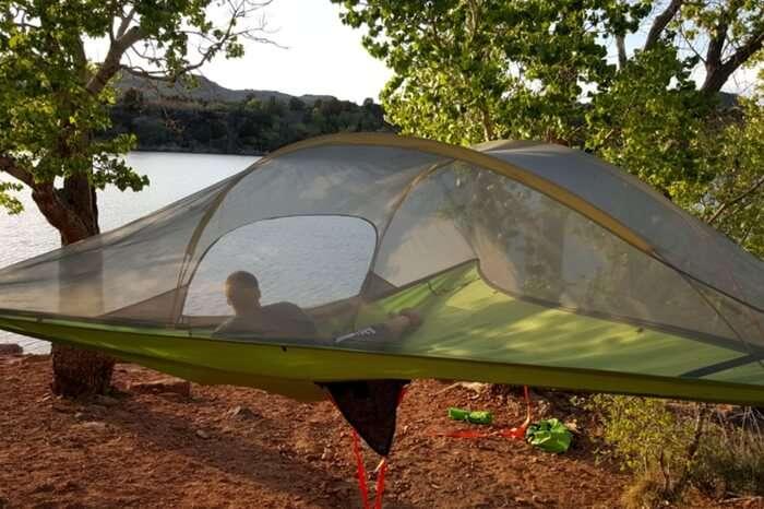 A traveler relaxing in a hammock tent