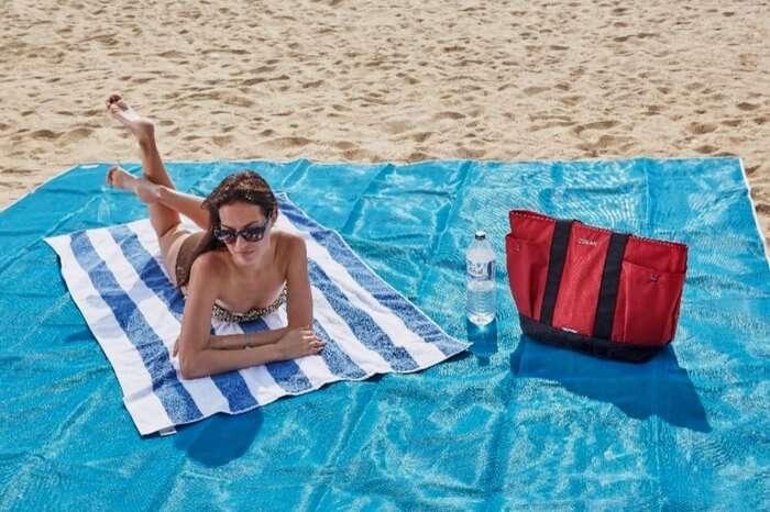 A woman sunbathing on a beach mat