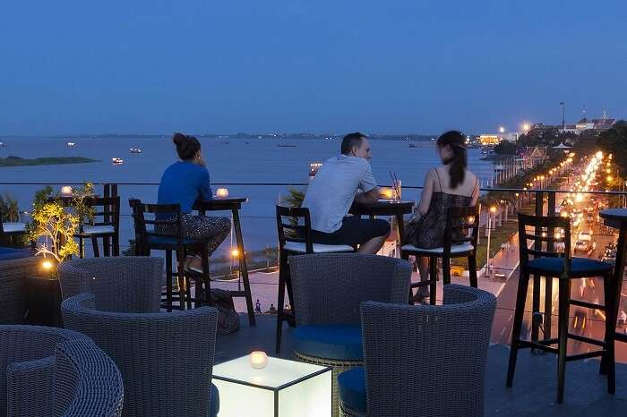 Guests enjoy drinks and snacks at a rooftop bar in Cambodia