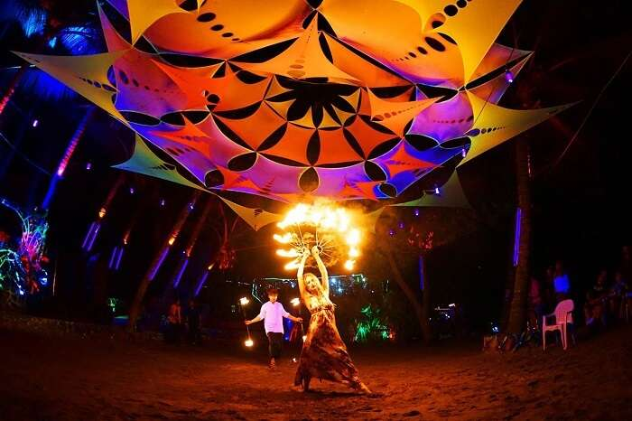 A performer dancing with fire at night at the Anjuna Beach