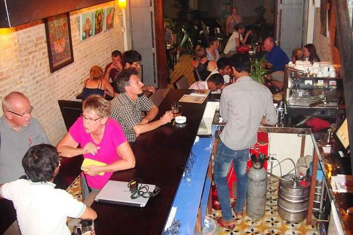 Locals at tourists interact over drinks and snacks at the Lotus Bar and Gallery in Cambodia