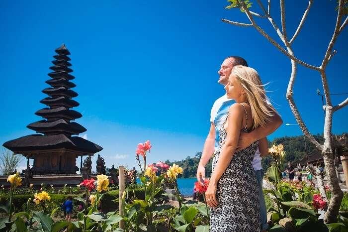 Honeymoon couple near the Balinese temple at beratan lake