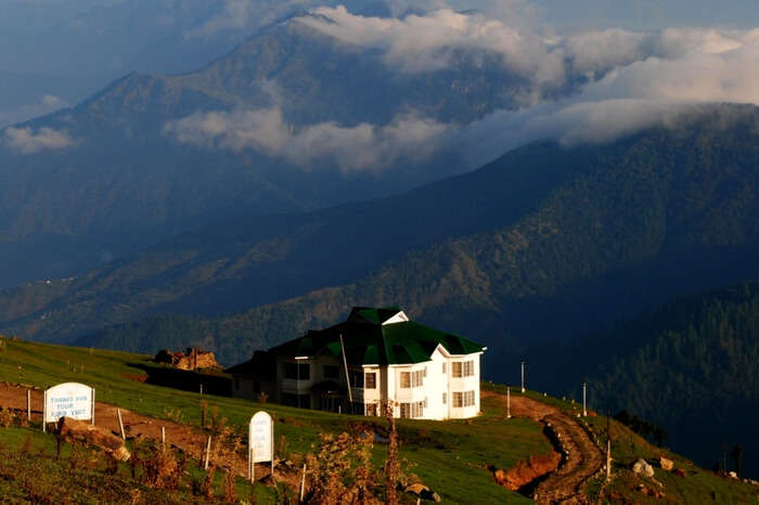 The beautiful guest house at Prashar Lake with Himalayas in the background