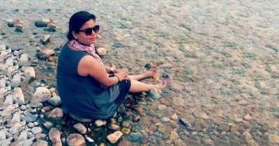 Nidhi sitting beside a stream in Jim Corbett