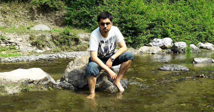 Tushar sitting by a stream during his trip to Lansdowne