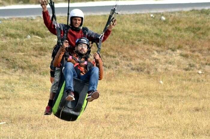 A man landing after his paragliding adventure