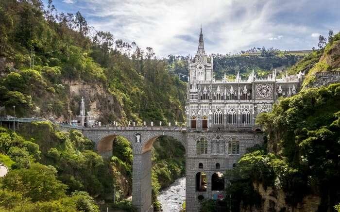 Shot of Las Lajas Sanctuary with hills, river and bridge